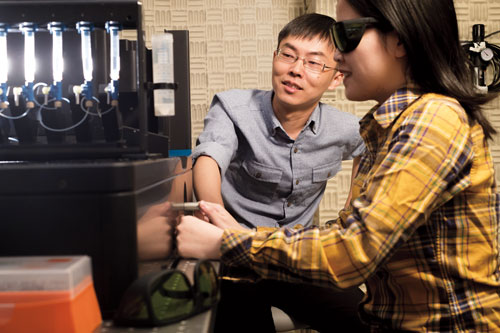 Liu (left) with postdoc Sai Li. The instrument they use to manipulate DNA is housed in a basement room with vibration-dampening walls. Photograph by Mario Morgado